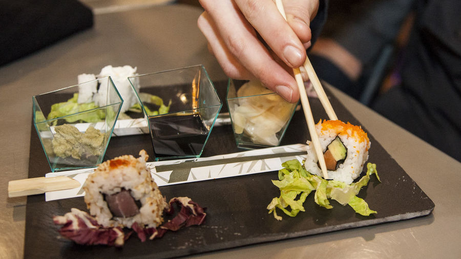Cropped Hand Holding Sushi With Chopsticks At Restaurant Table