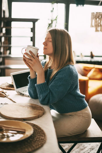 A young woman enjoys coffee in the morning and works at her laptop. work at home, online business,