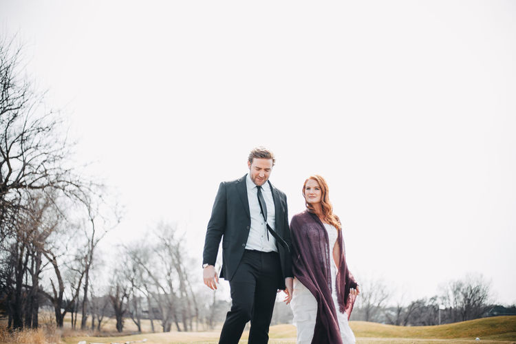Elegant Couple. A portrait of a young beautiful elegant couple outside holding hands and walking in field against white background. Formalwear Looking At Camera Majestic Suave Lifestyles Glamour Cool Attitude Three Quarter Length Two People Young Adult Couple - Relationship Redhead Beautiful People Staring Bare Tree Full Suit Looking Down Elégance Rural Scene White Background Copy Space Caucasian Confidence  Walking Holding Hands