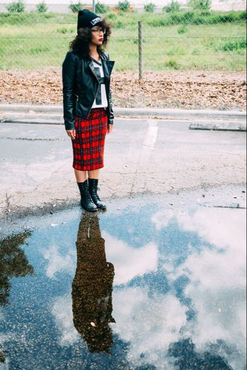 Full Length Of Woman Standing By Puddle On Street