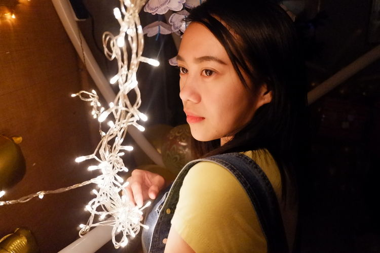 Close-up of young woman by illuminated string lights