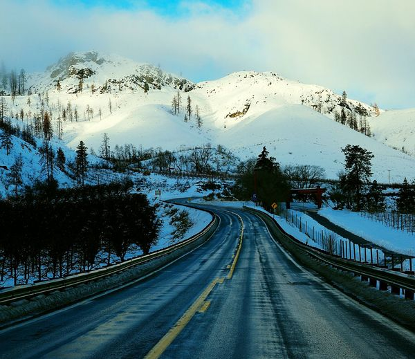 Country road passing through snow covered mountains against cloudy sky