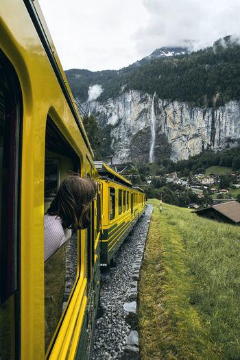 Woman peeking from train window passing by mountains