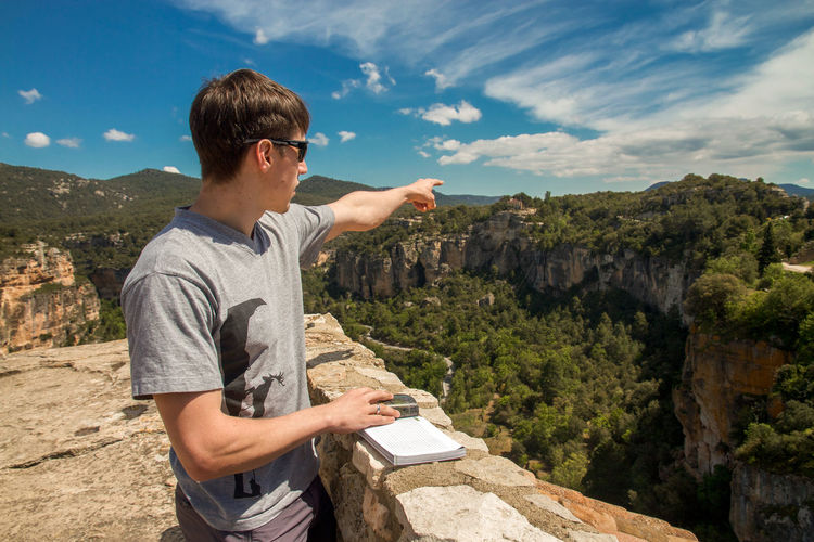 Young man pointing towards mountain during sunny day