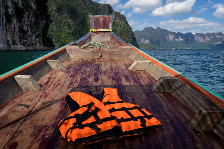 Life jacket with wood prow of a ship going on the sea.