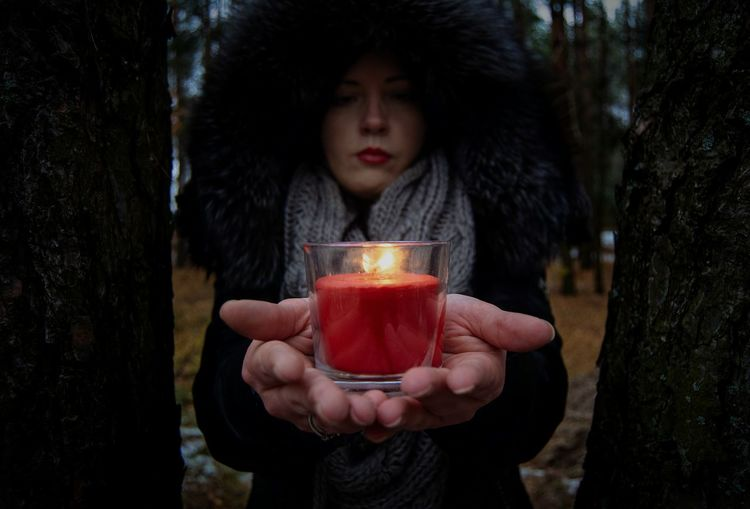Portrait Of Woman Holding Candle Outdoors