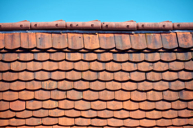 Low angle view of roof tiles against building