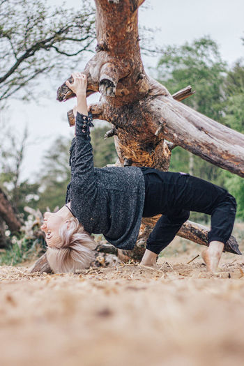 Full length of person on tree trunk