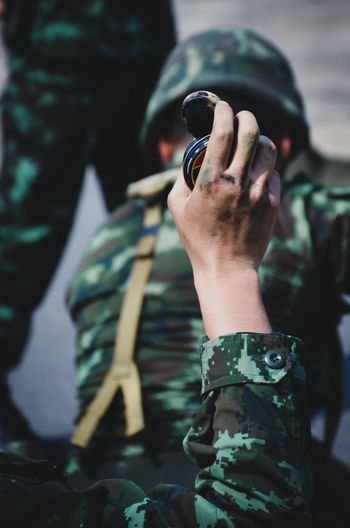 Cropped hand of army soldier holding equipment