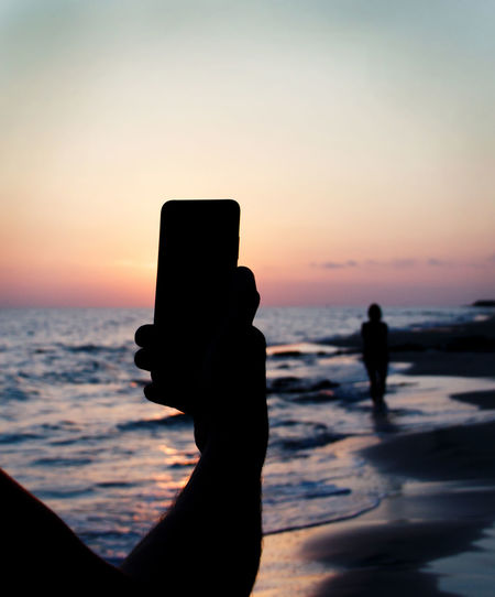 Silhouette person photographing sea against sky during sunset