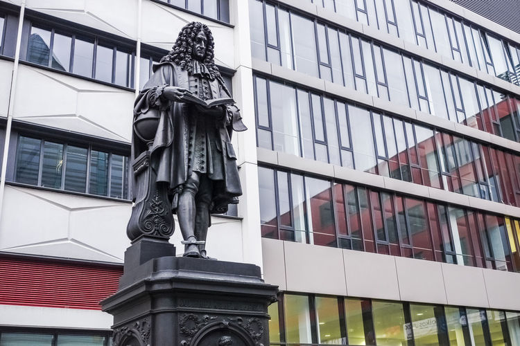 Statue of Gottfried Leibniz at the University campus in Leipzig, Germany. Gottfried Leibniz Statue Architecture Art And Craft Arts Culture And Entertainment Building Exterior Built Structure City Day Human Representation Leibniz  Low Angle View Male Likeness Mathematician No People Outdoors Philosopher Sculpture Statue Window