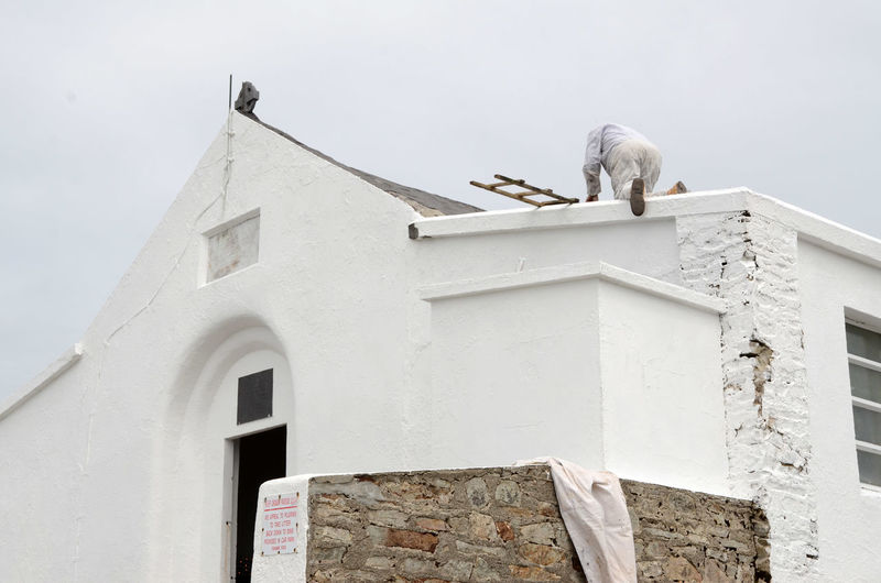 Construction Worker On Top Of Historic Building