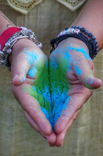 Midsection of girl holding powder paint during holi