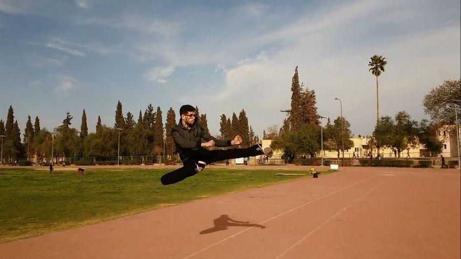 Man practicing karate kicking in mid-air against sky
