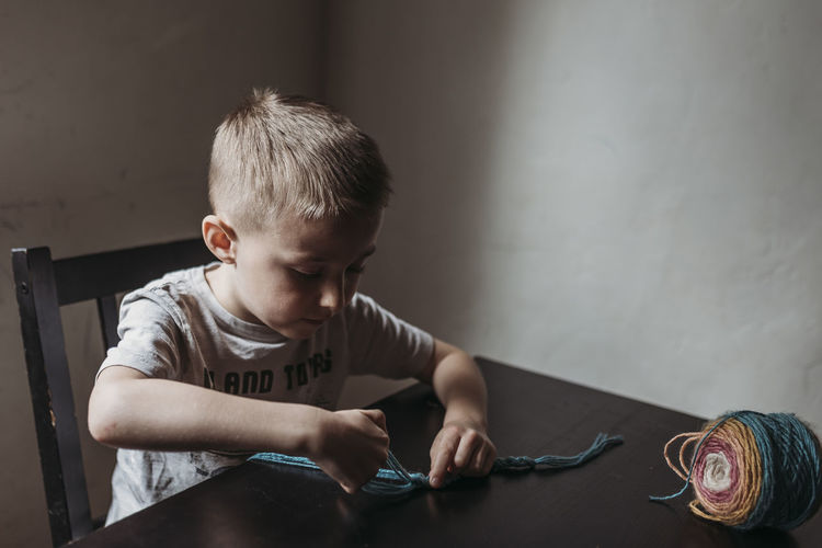 Cute boy playing on table at home