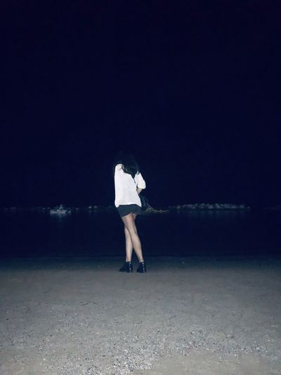 Rear view of woman standing at beach during night