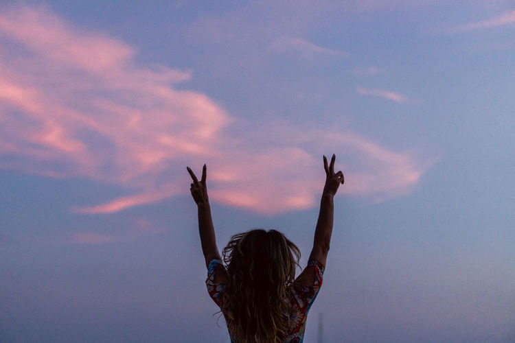 Rear view of woman with arms raised against sky
