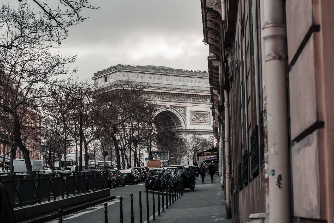 architecture, built structure, building exterior, arch, city, incidental people, transportation, triumphal arch, day, sky, mode of transportation, nature, building, outdoors, travel, land vehicle, motor vehicle, street, tree, history