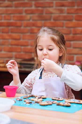 Cute girl tasting cookie on table in workshop