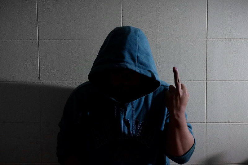 Man wearing hood gesturing standing against wall