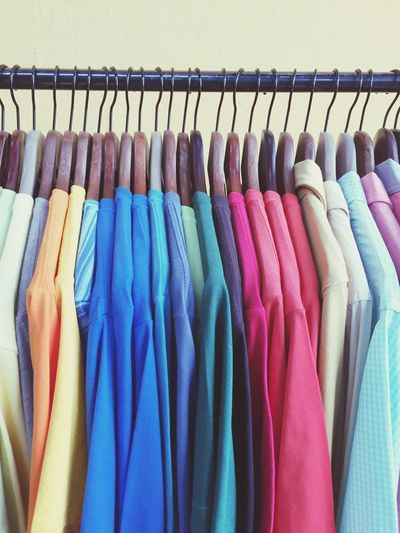 Close-up of shirts on coat hangers in row