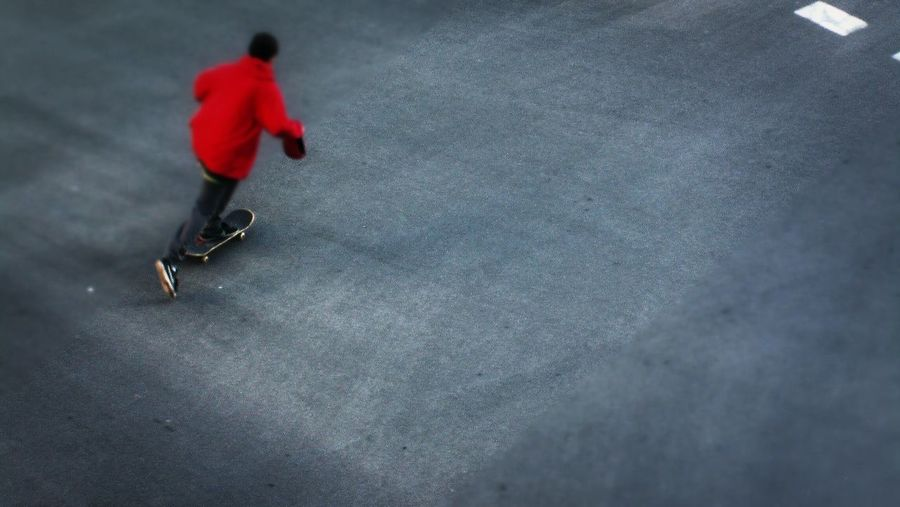 Close-up of road boy in red jacket skating fast