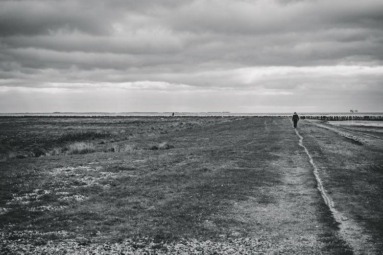 Rear view of person walking on field