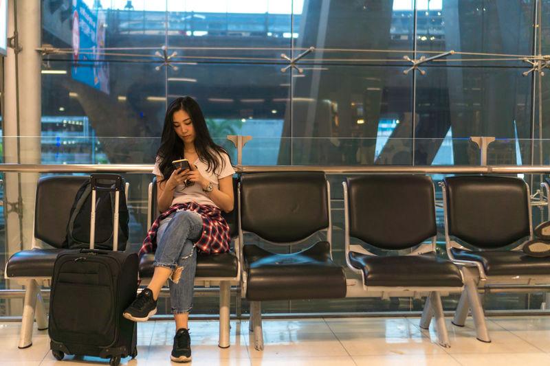 Full length of woman using mobile phone at airport