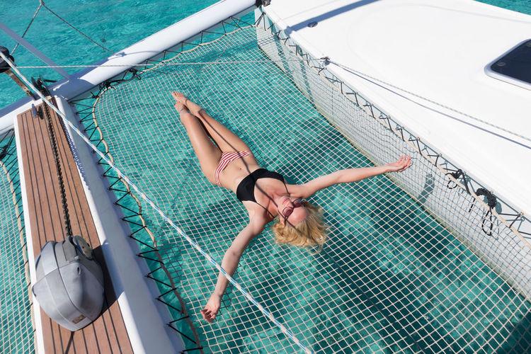High angle view woman lying on net over sea
