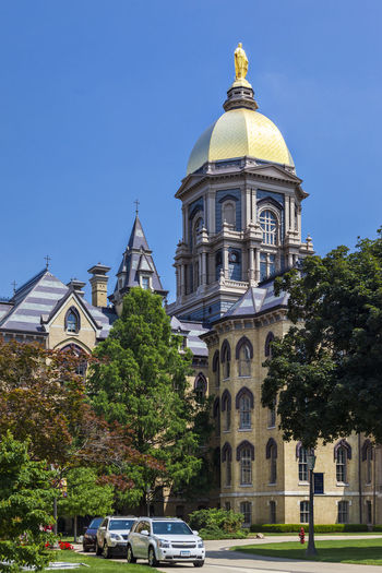 University of Notre Dame USA Outdoor Campus Famous Green Knowledge Tree Blue Sky Christian Color Culture Education Green Grass Religion Science And Technology Vertical Composition Golden Tower Building Lawn Main Building Sunny Day University Of Notre Dame USA