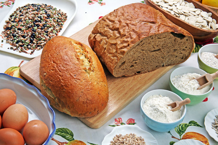 High Angle View Of Grains, Flour, And Bread On Tablecloth