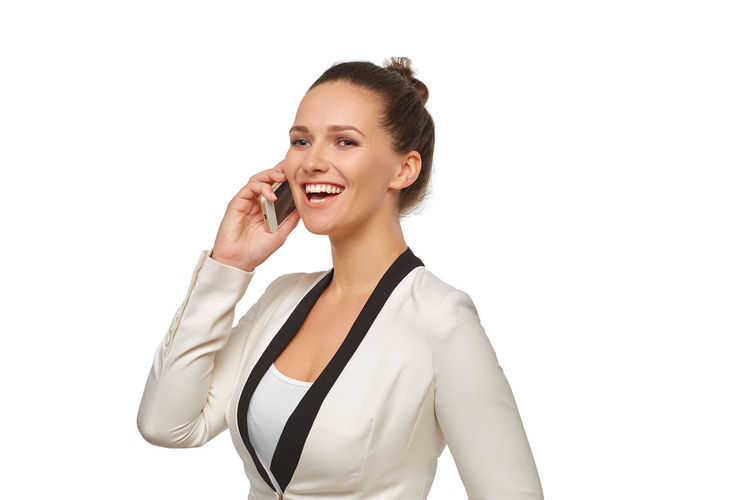Smiling young woman using smart phone against white background