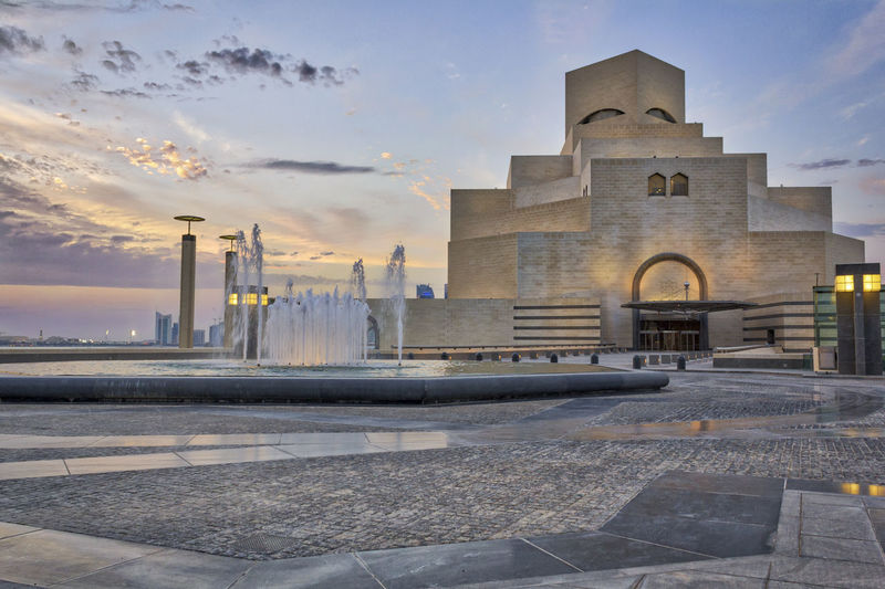 Museum of Islamic Art , Doha,Qatar in daylight exterior view with fountain in foreground and clouds in the sky in the background Architecture Built Structure Sky Building Exterior Cloud - Sky No People Museum Of Islamic Art , Doha,Qatar Doha Qatar Islamic Architecture Islamic Art Sunset Building Water Islamic Culture Arabian Gulf History City Outdoors Fountain Day Landmark Attractive Heritage
