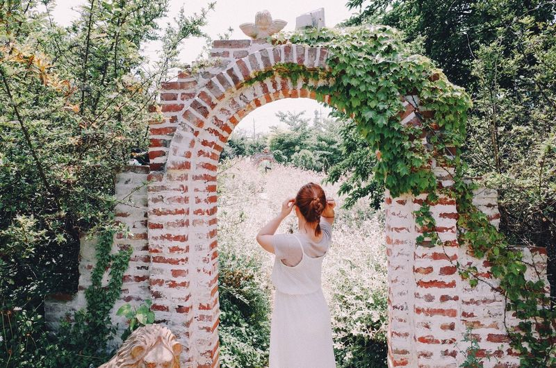 Rear View Of Woman Standing Amidst Archway