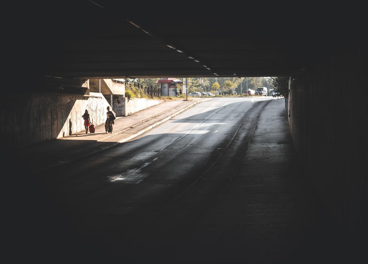 PEOPLE WALKING ON ROAD ALONG TUNNEL