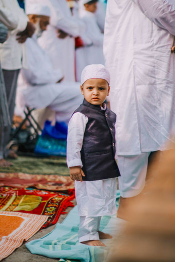 Portrait of cute boy in traditional clothing standing on mat