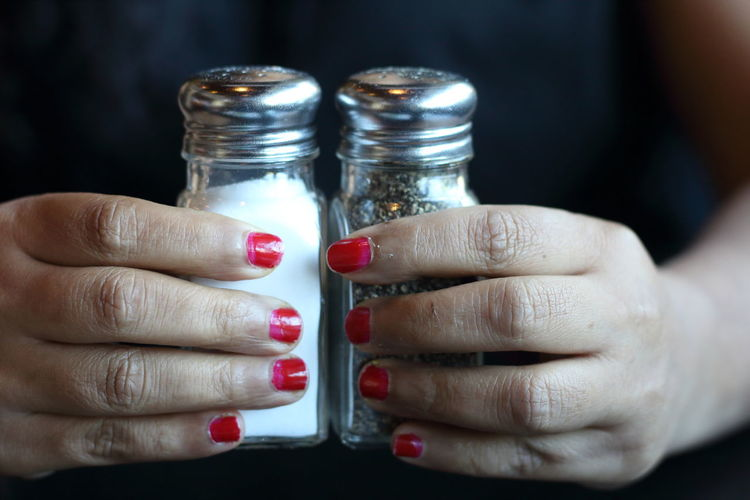 Midsection of woman holding salt and pepper shakers