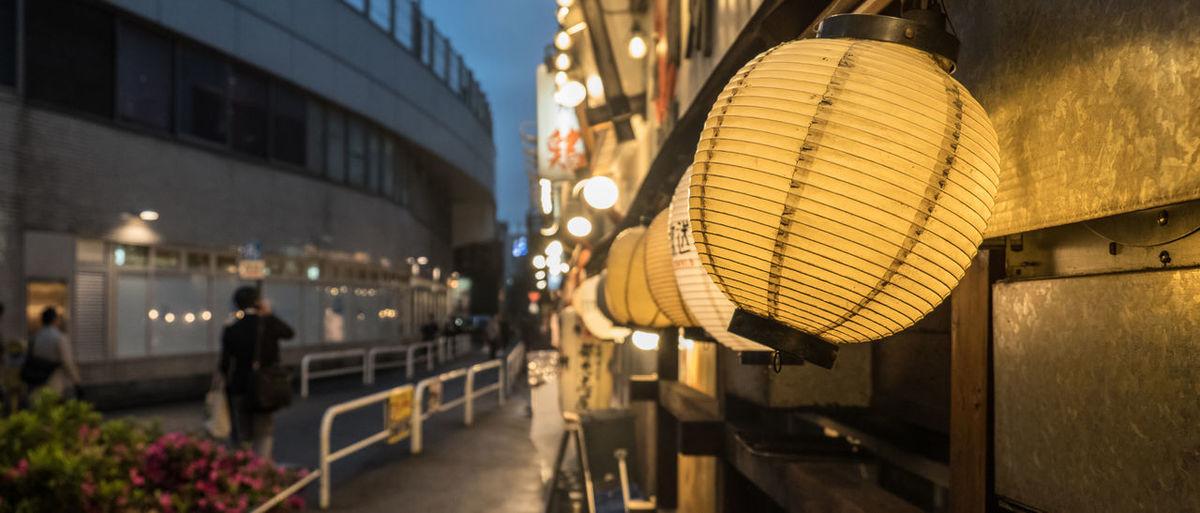 Illuminated japanese lantern hanging on building at dusk