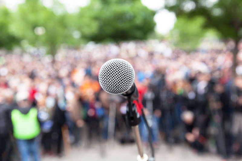 Close-up of microphone against crowd in city