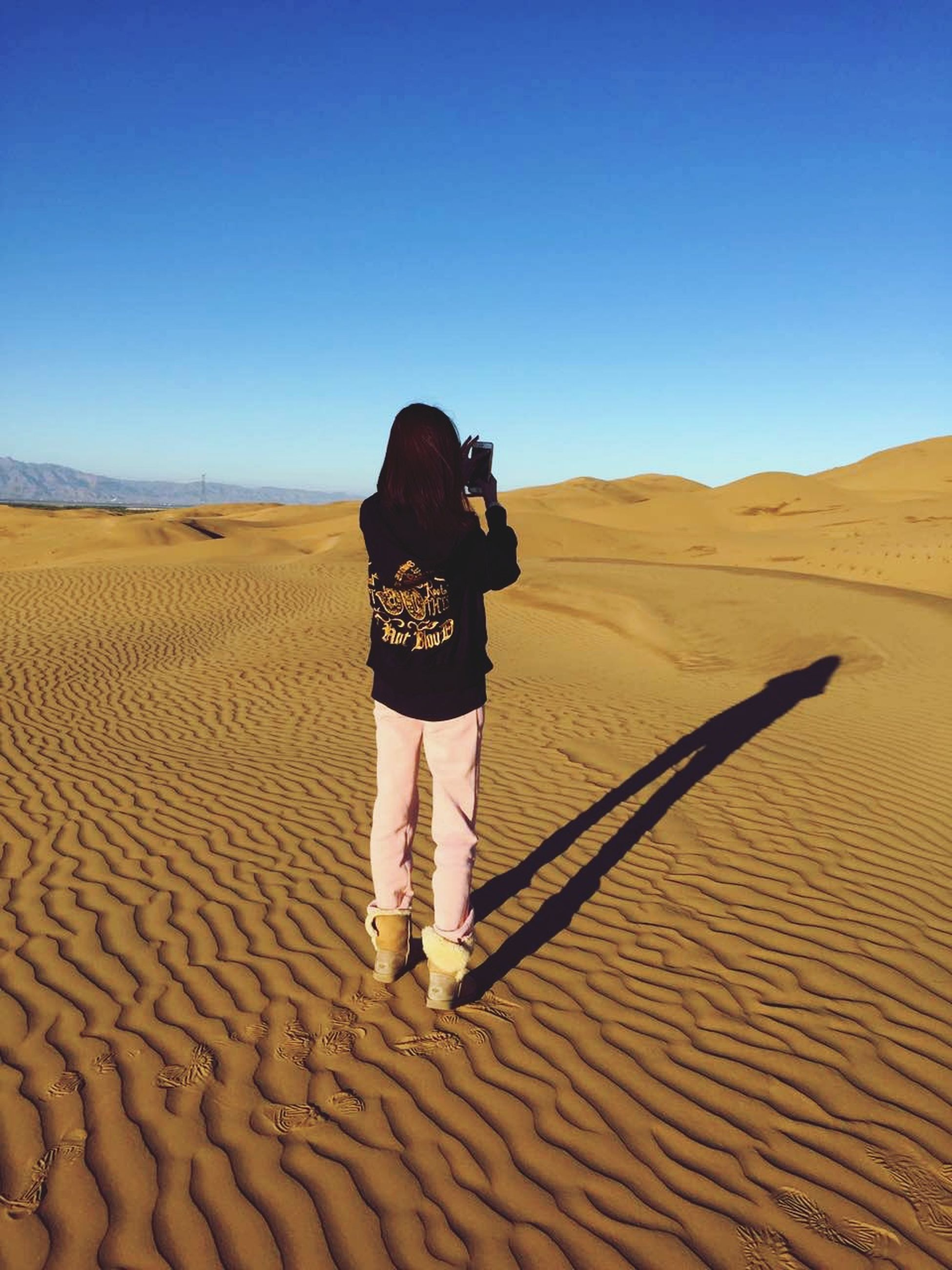 clear sky, sand, landscape, desert, sand dune, full length, lifestyles, tranquil scene, leisure activity, arid climate, tranquility, blue, copy space, rear view, horizon over land, casual clothing, scenics, nature