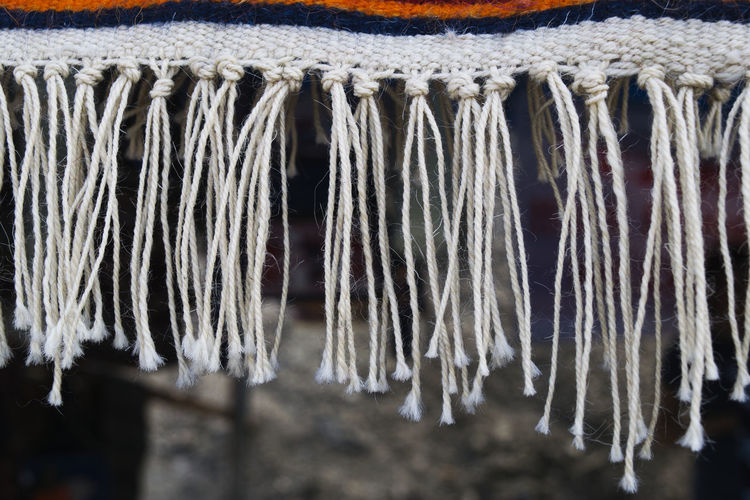 Close-up of tassels hanging from rug