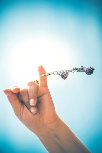 Cropped image of woman spinning key ring against clear blue sky