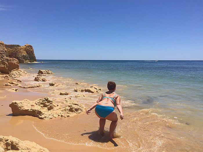 Rear view of woman in bikini bending at seashore against sky
