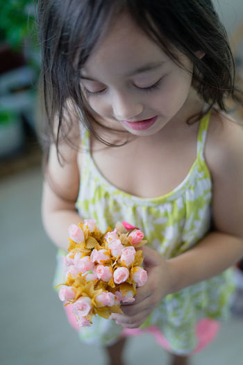 Close-up of girl holding flowering plant