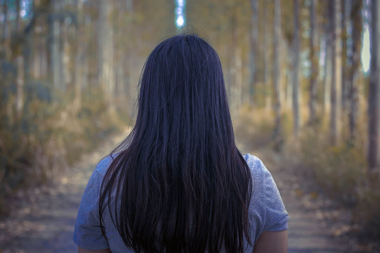 Rear view of woman with long hair standing against trees in forest