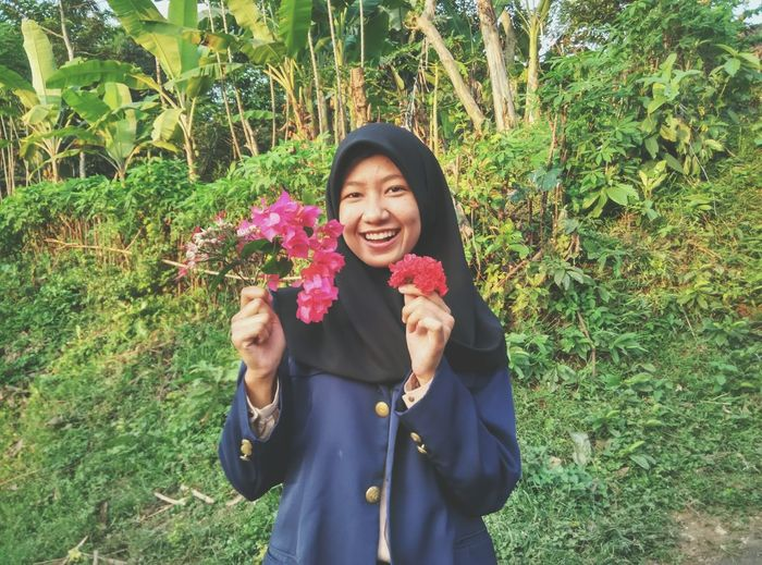 Portrait of happy woman holding flowers against trees