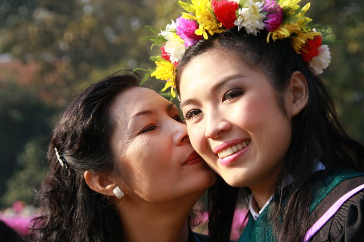 Close-up of mother kissing daughter in sunny day