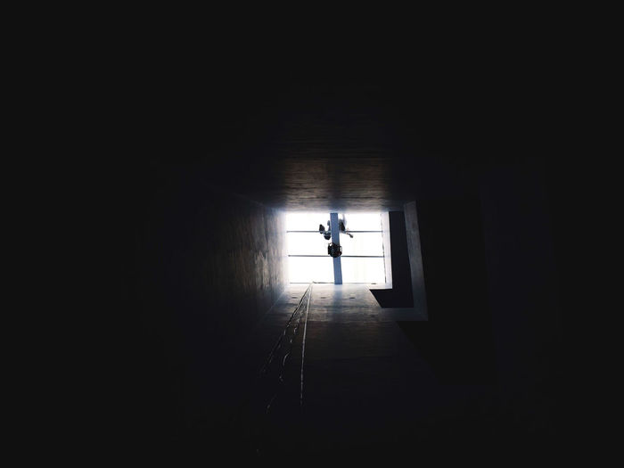 Silhouette man walking in corridor of building