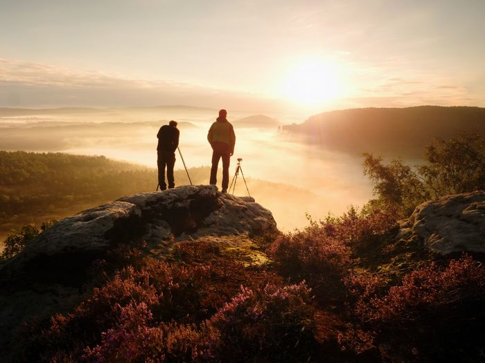 Photographers stay on cliff and takes photos. dreamy foggy mountains, orange misty sunrise in land