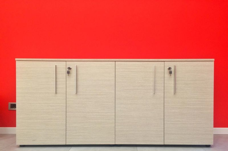 Cabinet against red wall in office